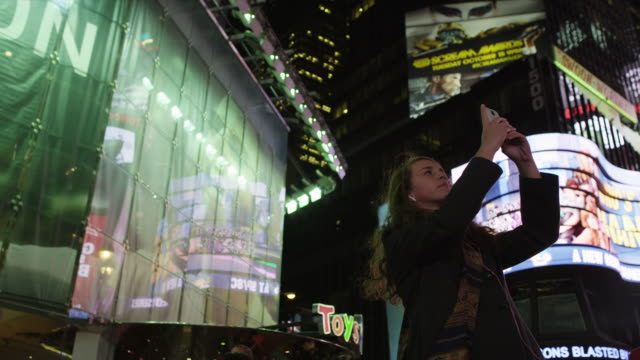 slo mo ms la teenage girl photographing on time square at night / manhattan, new york city, new york state, usa - contented emotion stock videos & royalty-free footage