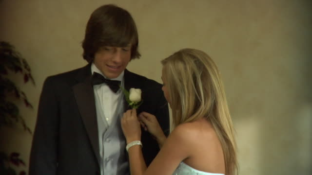 cu, teenage girl (16-17) pining flowers to her prom date's jacket, edison, new jersey, usa - coppia di adolescenti video stock e b–roll