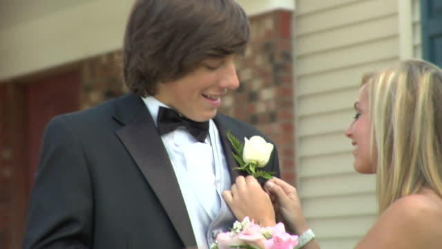 cu, teenage girl (16-17) pining flowers to her prom date's jacket in front of house, edison, new jersey, usa - teenagerpaar stock-videos und b-roll-filmmaterial