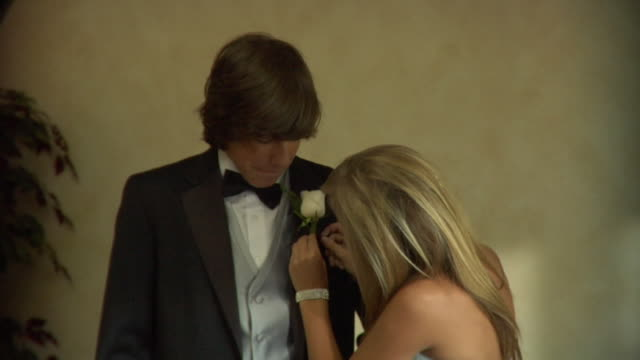 cu, teenage girl (16-17) pining flowers to her prom date's jacket, portrait, edison, new jersey, usa - coppia di adolescenti video stock e b–roll
