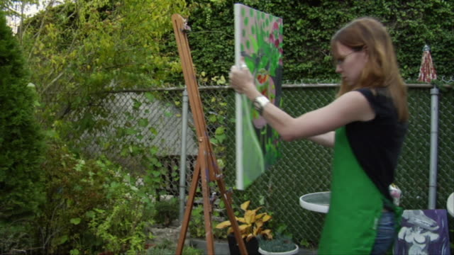 MS, Teenage girl (16-17) placing painting on easel in garden, Brooklyn, New York City, New York, USA, HA