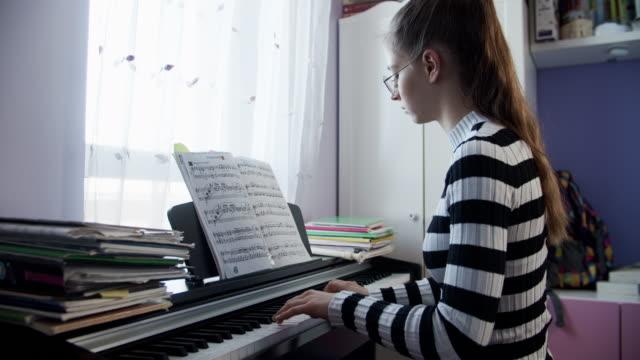 teenage girl playing digital piano - imgorthand stock videos & royalty-free footage