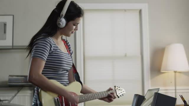 vídeos de stock, filmes e b-roll de ms pan teenage girl (16-17) playing electric guitar in home / orem, utah, usa - guitarist