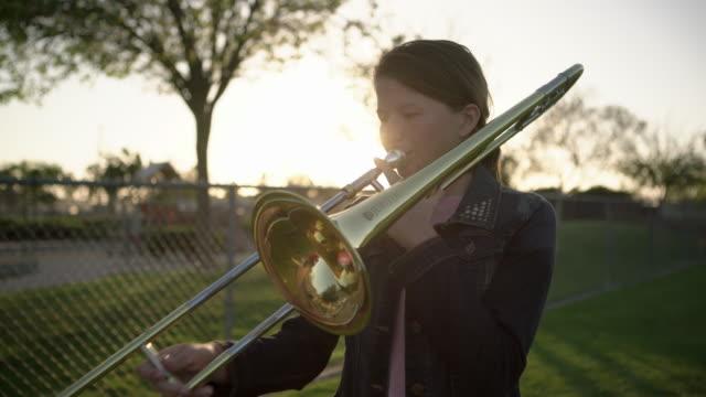 ms teenage girl playing her trombone in a field - trombone stock videos & royalty-free footage
