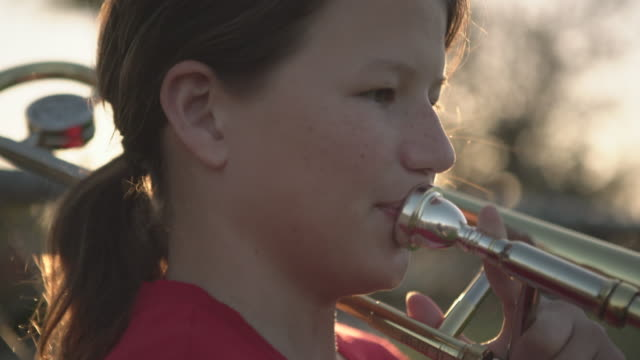 stockvideo's en b-roll-footage met cu teenage girl playing her trombone outdoors - muziekgroepen
