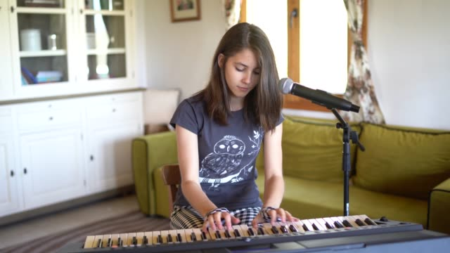 teenage girl playing piano and singing at home - singing stock videos & royalty-free footage