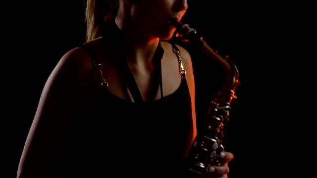 stockvideo's en b-roll-footage met tienermeisje spelen saxofoon - saxofonist