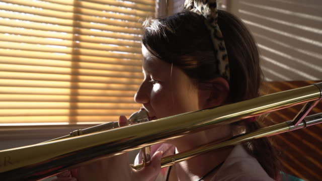 cu teenage girl playing trombone in her bedroom - haar nach hinten stock-videos und b-roll-filmmaterial