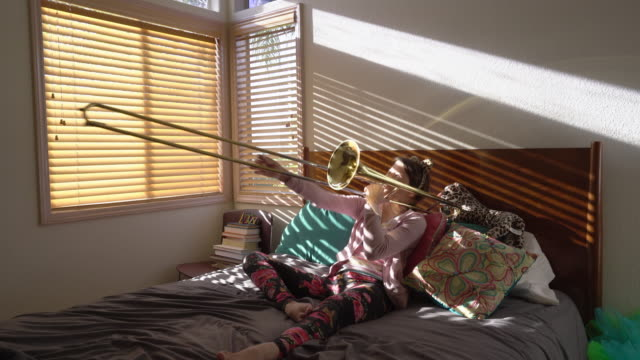 WS Teenage girl playing trombone in her bedroom