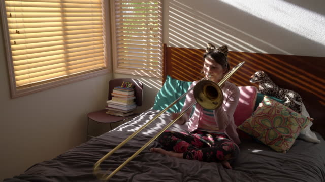 ms teenage girl playing trombone in her bedroom - hair accessory stock videos and b-roll footage