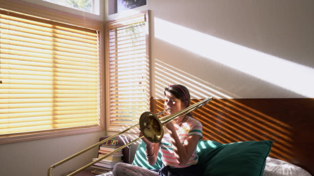 MS Teenage girl playing trombone in her bedroom