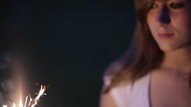 teenage girl playing with sparkler at dusk - endast en tonårsflicka bildbanksvideor och videomaterial från bakom kulisserna
