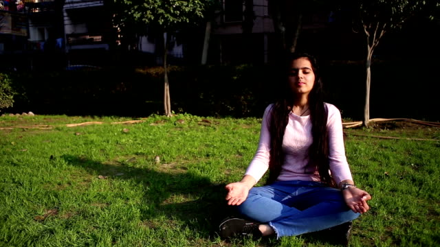 teenage girl practicing yoga performing gyan mudra and lotus position outdoors with closed eyes. - 16 17 years stock videos & royalty-free footage