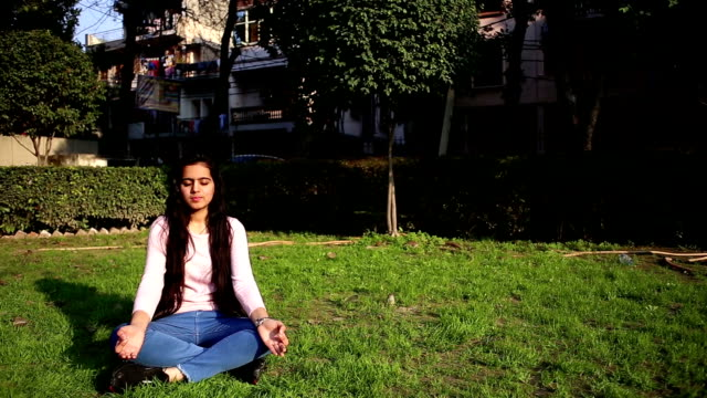 teenage girl practicing yoga performing gyan mudra and lotus position outdoors with closed eyes. - lotus position stock videos & royalty-free footage