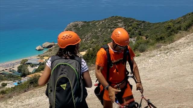vidéos et rushes de adolescente, préparation pour le parapente au sommet de la colline - parachute