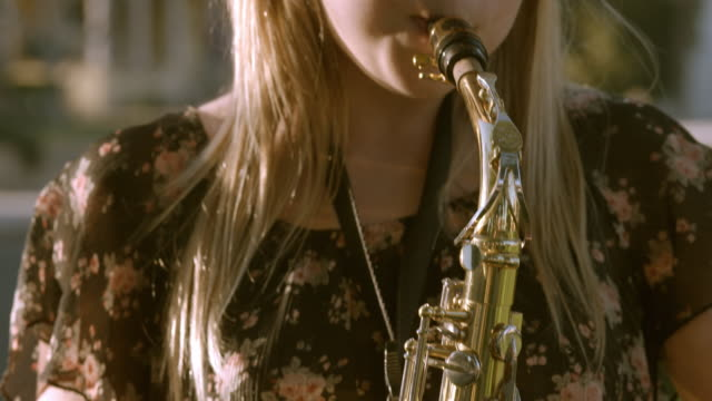 cu pan teenage girl pressing air into mouthpiece of saxophone while her fingers hit upper and lower register keys / redlands, california, usa - saxophone stock videos and b-roll footage