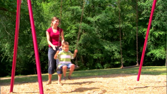 teenage girl pushing boy on a swing - 子守り点の映像素材/bロール