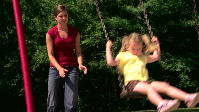 teenage girl pushing girl on a swing - 子守り点の映像素材/bロール