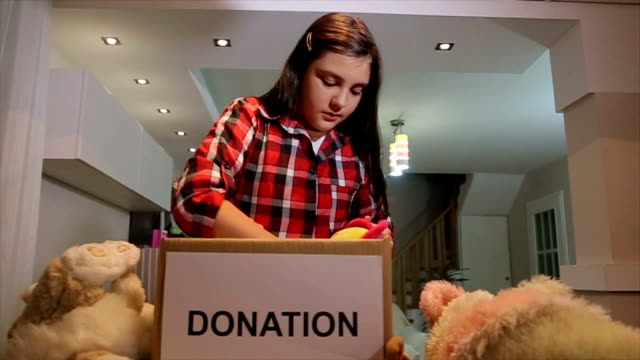 teenage girl put toys in donation box for other children - altruism stock videos & royalty-free footage