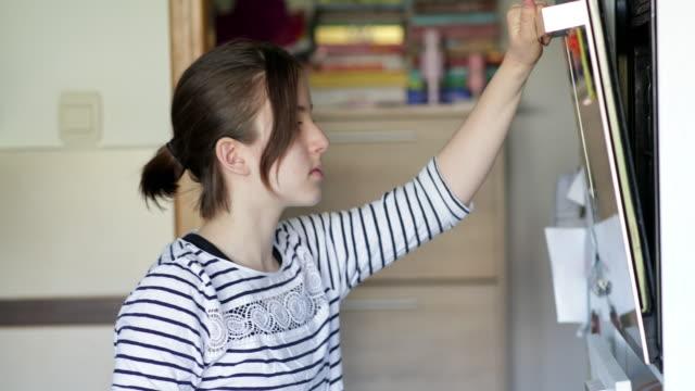 10代の女の子は焼くためにジャガイモとベーキングパンを置きます - オーブンの天板点の映像素材/bロール