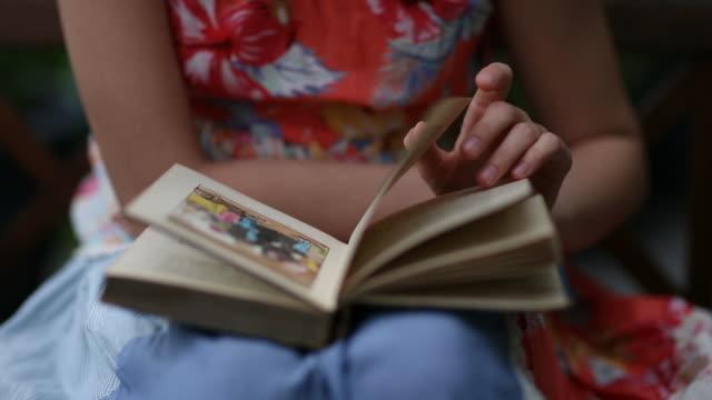 teenage girl reading a book outdoors - one teenage girl only点の映像素材/bロール
