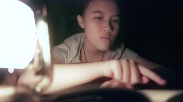 teenage girl reading book with lantern at night - lantern stock videos & royalty-free footage