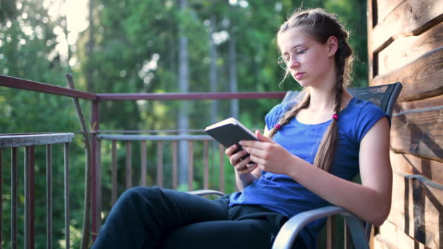 teenage girl reading ebook on cabin's balcony - solo adolescenti femmine video stock e b–roll