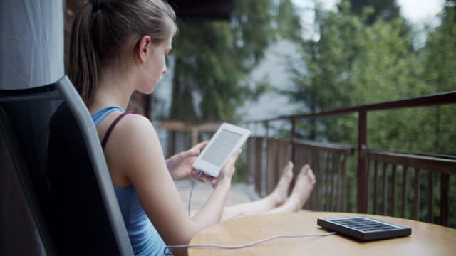 teenage girl reading ebook on cabin's balcony - one teenage girl only stock videos & royalty-free footage