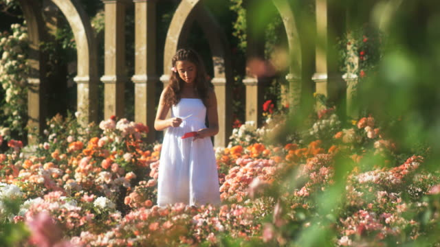 vídeos de stock, filmes e b-roll de slo mo ws teenage girl (16-17) reading letter in summer garden, lehi, utah, usa - lehi