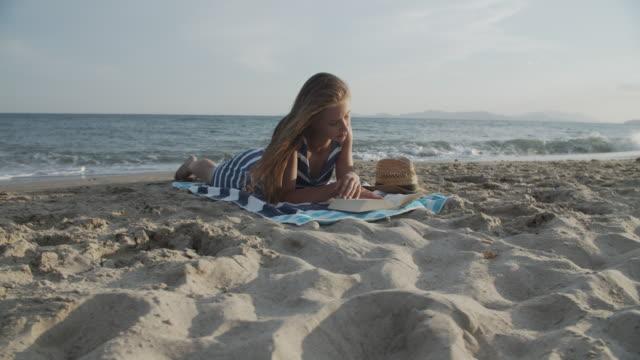vídeos de stock, filmes e b-roll de adolescente lendo na praia - toalha de praia