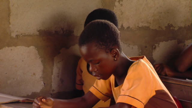 MS Teenage girl reading sitting at desk in classroom, Tamale, Ghana