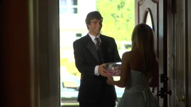 MS, Teenage girl receiving (16-17) corsage from teenage boy (16-17) in doorway, Edison, New Jersey, USA