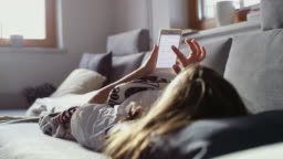 MS Teenage girl relaxing on sofa with smart phone