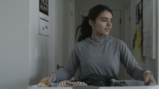 teenage girl removing laundry from washing machine then carrying clothing in basket / lehi, utah, united states - tvätt bildbanksvideor och videomaterial från bakom kulisserna