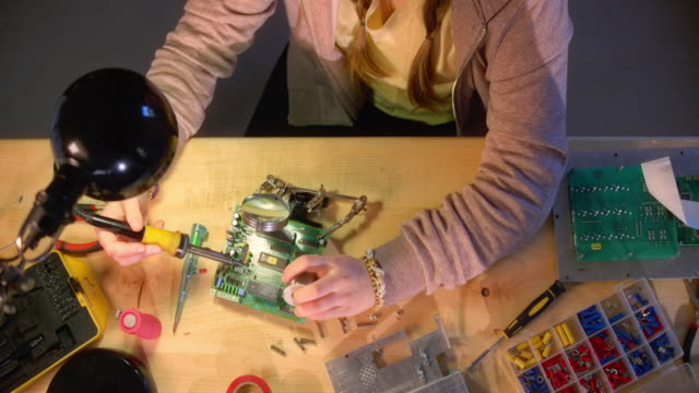 slo mo ld teenage girl repairing a motherboard with a soldering iron and wire - table top view stock videos & royalty-free footage