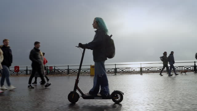 teenage girl ridin e scooter along seafront past walkers, backlit with reflection - female high school student stock videos & royalty-free footage