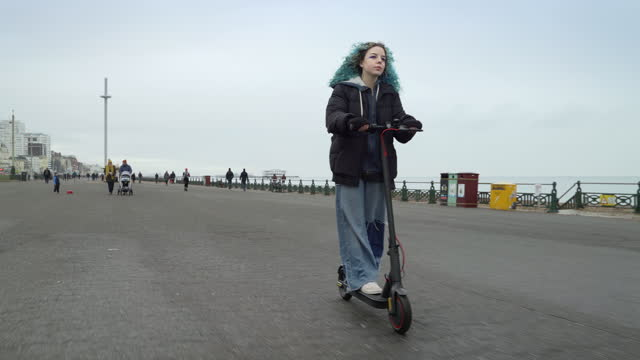 teenage girl riding e scooter along seaside path - female high school student stock videos & royalty-free footage