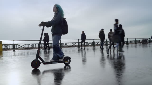 teenage girl riding e scooter on seafront on rainy day, past walkers - female high school student stock videos & royalty-free footage