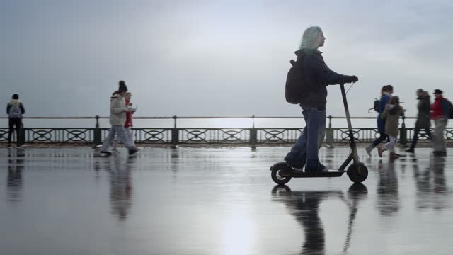 teenage girl riding e scooter on seafront on wet day in and out of frame - female high school student stock videos & royalty-free footage
