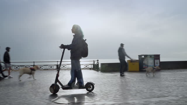 teenage girl riding e scooter on seafront on wet day - female high school student stock videos & royalty-free footage