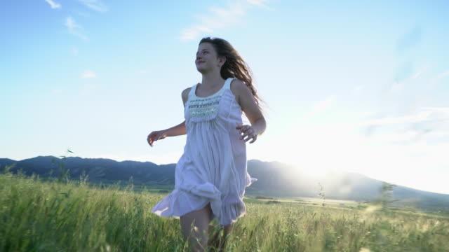 WS SM TS Teenage girl running through a field at sunset.