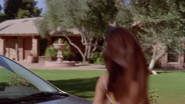 Teenage girl running up to new car and leaning over hood / smiling and dangling keys at camera