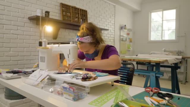 covid-19のための十代の少女の縫製と切断マスク - one teenage girl only点の映像素材/bロール