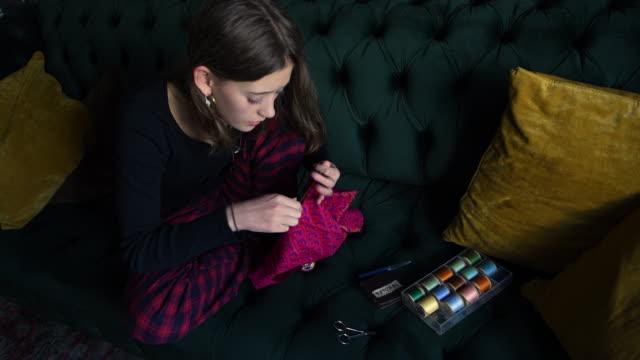 teenage girl sewing at home on the sofa - 美術工芸品点の映像素材/bロール