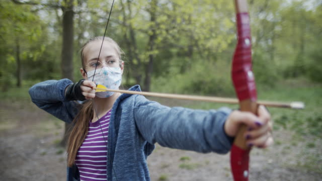 teenage girl shooting a bow in the forest during covid-19 pandemic - taking a shot sport stock videos & royalty-free footage