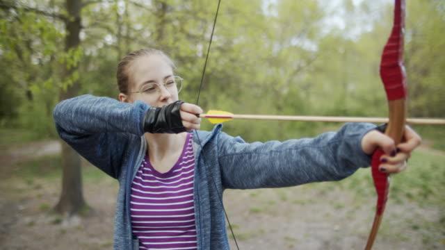 vidéos et rushes de adolescente tirant un arc dans la forêt - viser