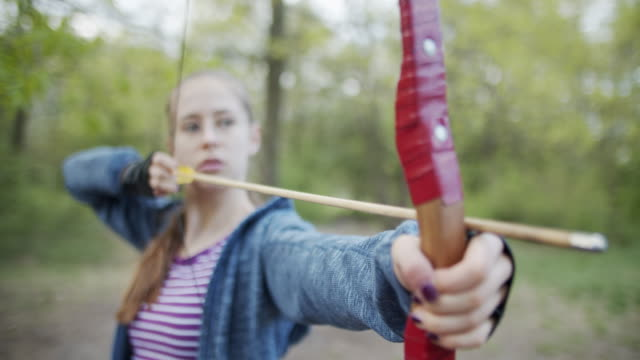teenage girl shooting a bow in the forest - accuracy stock videos & royalty-free footage