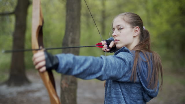 teenage girl shooting a bow in the forest - females stock videos & royalty-free footage