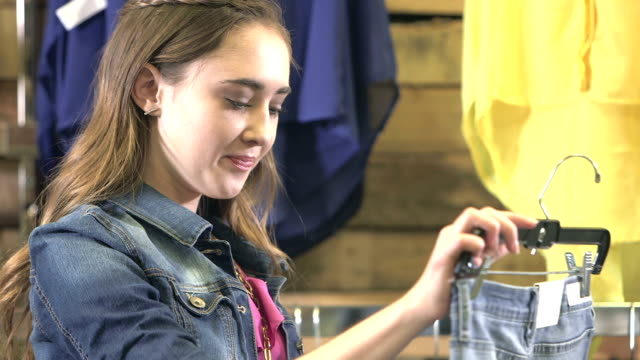 teenage girl shopping for jeans in clothing store - pants stock videos & royalty-free footage