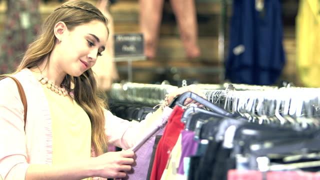 vídeos de stock e filmes b-roll de teenage girl shopping in clothing store - preço